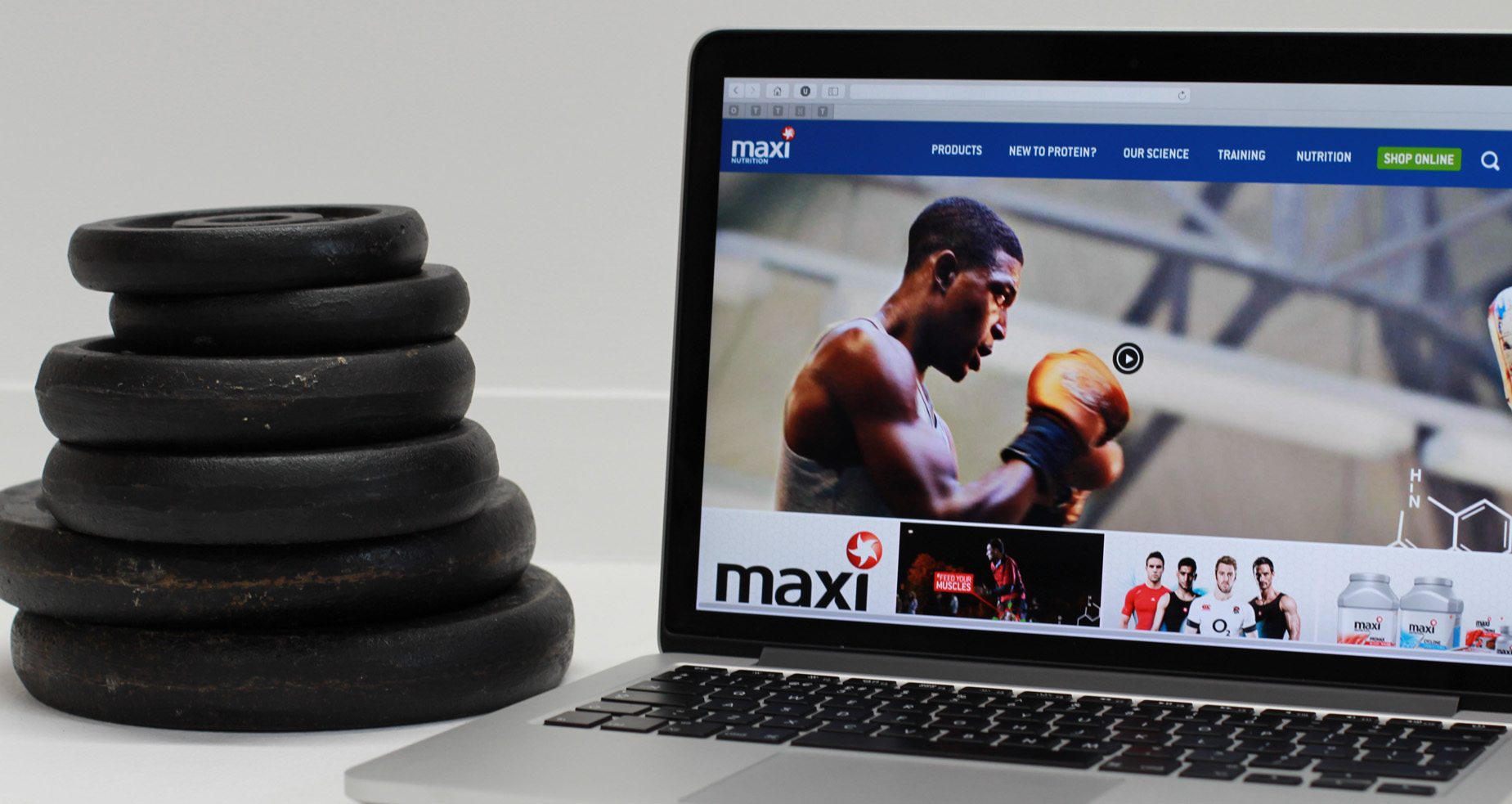 MaxiNutrition responsive website on a MacBook next to a stack of weights