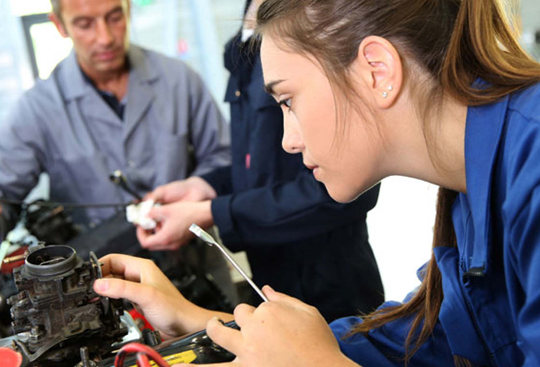 Female Mechanic repairing a carburettor on a car engine