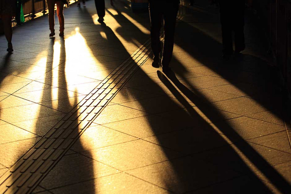 People casting shadows across the ground at sunset in the city