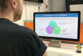 Jordan looks at a customer connection slide on a MacBook